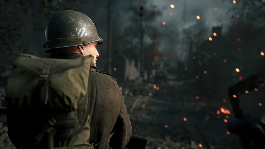 A soldier looks on at a burning forest in front