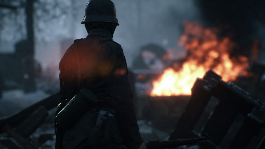 A soldier stands in front of the camera looking across the battlefield with a fire in the distance.