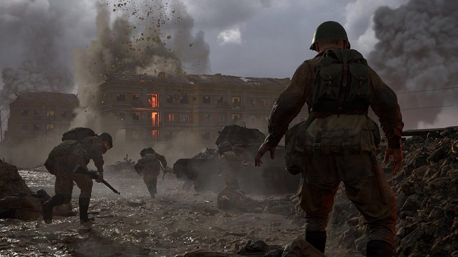 A soldier stands overlooking a battlefield as soldiers run in front of him in all directions.
