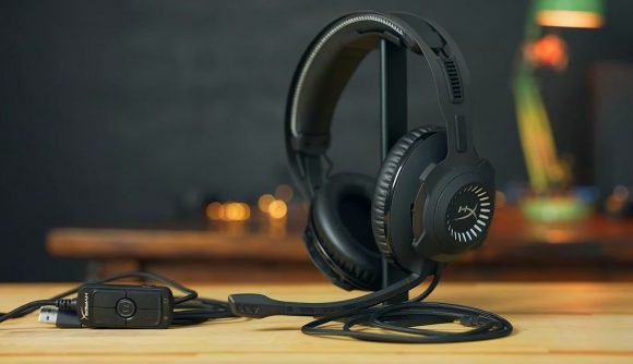A black HyperX headset sitting on its stand on a wooden table top