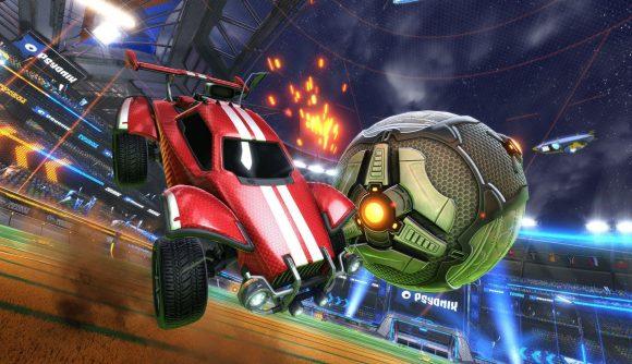 A red Rocket League car sideswipes the ball