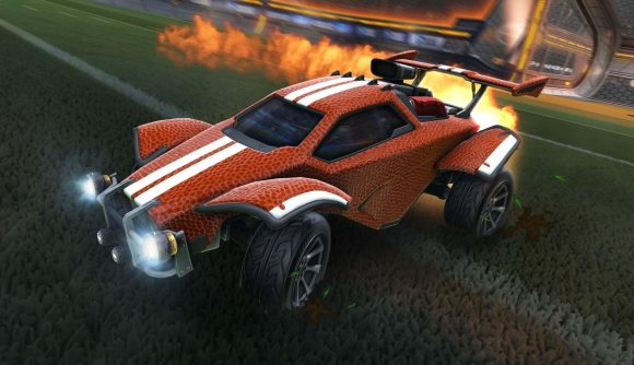 A Rocket League car sporting a burnt orange and white skin boosts away up the pitch