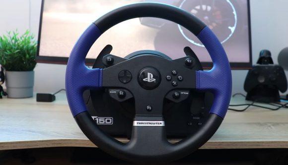 A blue an black racing wheel controller mounted on a wooden desk
