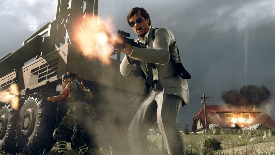 An operator in black sunglasses and a white suit shouts and fires an assault rifle. A house explodes on the background