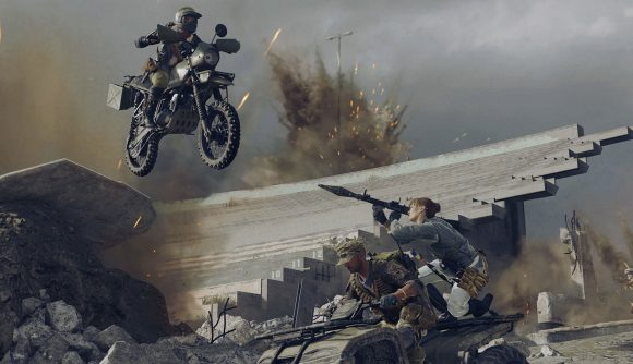 A person on the back of a quad bike tries to shoot someone riding a bike with a rocket launcher