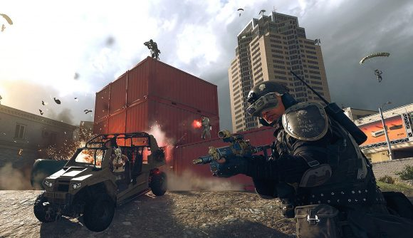An operator in black military gear draws his weapon. Behind him, another operator is driving a buggy, and players are firing weapons from on top of a stack of red shipping containers
