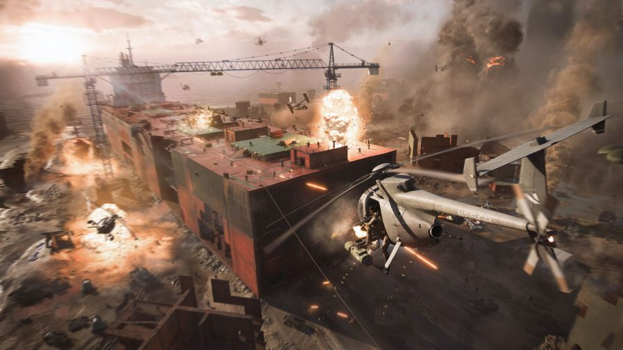 Battlefield 2042 Hazard Zone Own Map: A sandy battlefield can be seen below with helicopters flying above people shooting each other on rusted out metal buildings.
