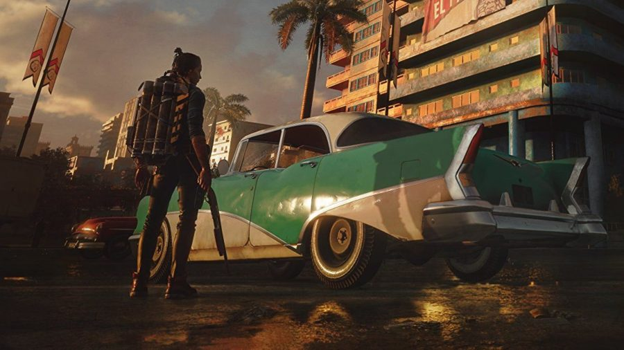 Far Cry 6 best mods: Dani stands in front of a car, looking up at a building.